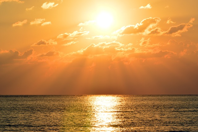 Solkrem er viktig ved sol og lettskyet vær. Her en solnedgang over havet.